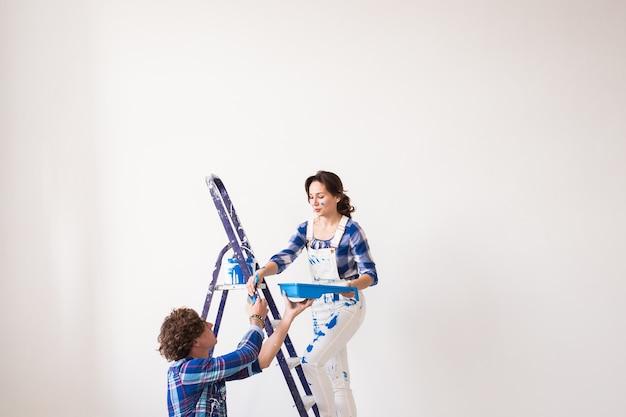 Молодая семья вместе ремонтирует и красит стены и смеется.