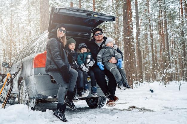 暖かい服を着た若い家族は、昼間の冬の森の車のトランクに座っているカメラでポーズをとる。