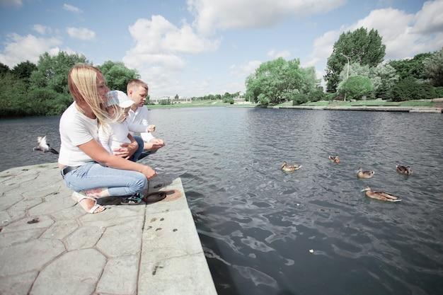 Молодая семья кормит диких уток, сидя на пирсе у озера