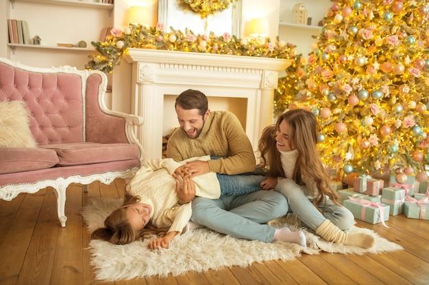 Молодая семья чувствует себя счастливым открытием рождественских подарков