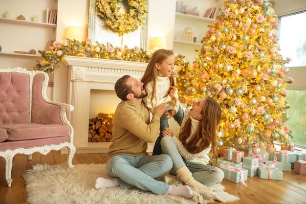 新年のツリーの近くに座って幸せな若い家族