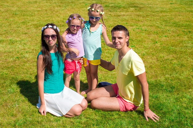 Young family of four sitting on the grass and have fun