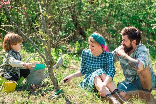Молодая семья, занимающаяся садоводством в саду, семейная посадка