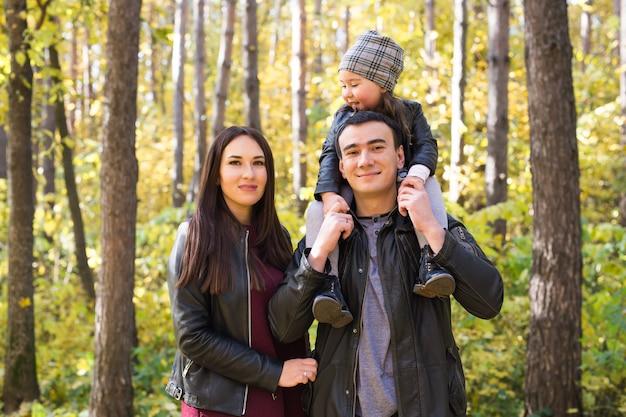 秋の公園で幸せな若い家族