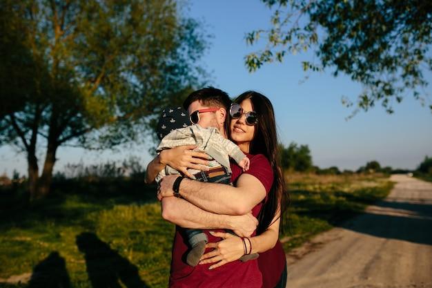 若い家族は田舎で屋外で楽しんでリラックスしています