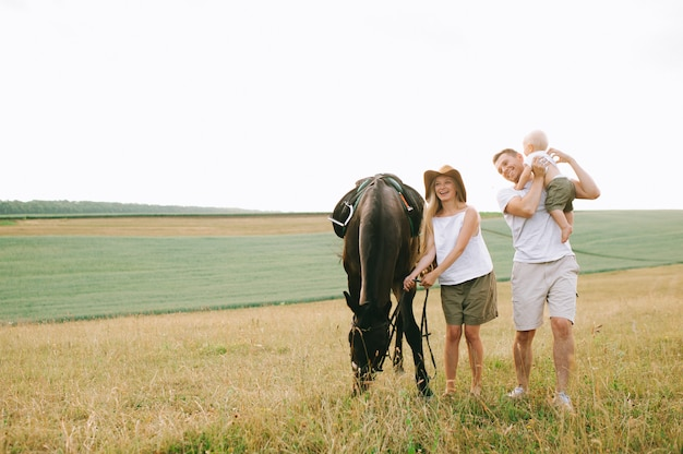 A young family have a fun in the field. parents and child with a horse