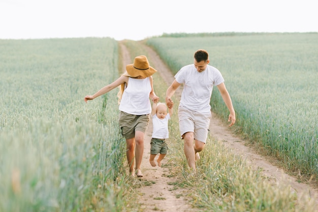 A young family have fun with their little baby in the field