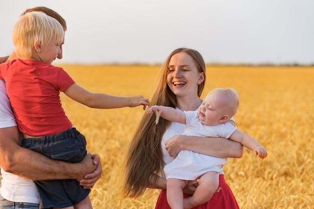 재미 ourdoors 젊은 가족. 엄마 아빠와 밀밭에 두 아이. 생활 양식