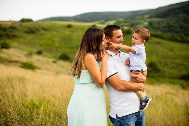 Молодая семья весело на открытом воздухе в летнем поле