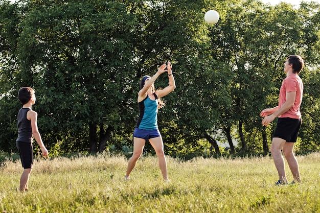 Молодая семья весело играет с мячом