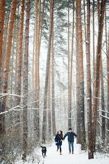 Молодая семья весело с собакой в зимней деревне на каникулах. скопируйте пространство для текста. выборочный фокус.
