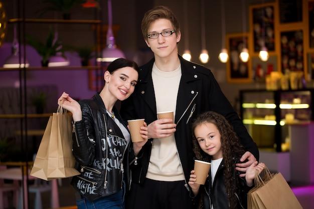 ショッピングの後、カフェで時間を過ごしている若い家族。ママ、パパ、娘はお茶とカフェを飲みます。買い物の後、カフェで過ごす家族