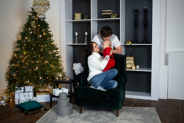 Young family at home at christmas time near beautifully decorated christmas tree