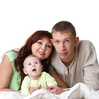 Молодая семья в постели: ребенок, мужчина, женщина