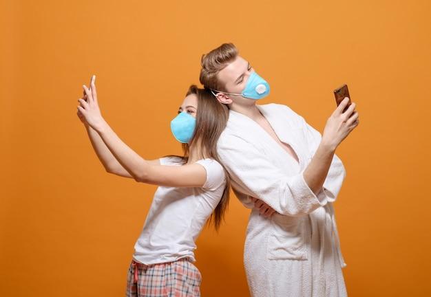 Молодая семья в домашней одежде на желтом апельсине в карантине хорошие семейные отношения, мужчина и женщина в медицинских масках вместе, общение в социальных сетях