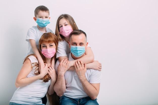 Молодая семья в медицинских масках во время домашнего карантина.