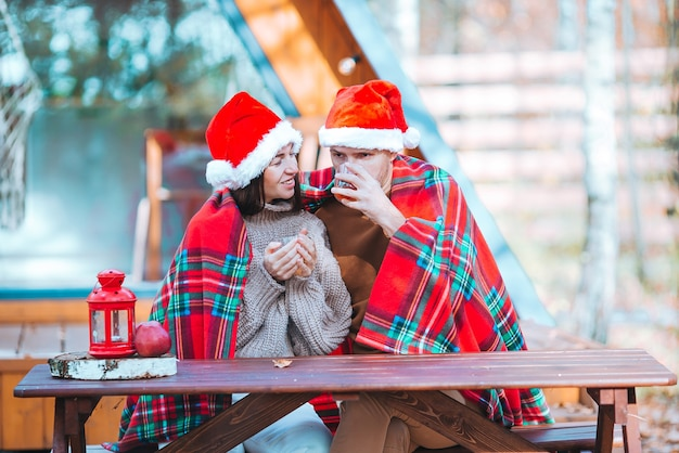 그들의 집의 나무 이전 테이블에 앉아 산타 모자에 젊은 가족