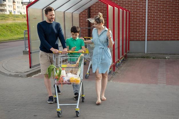 젊은 가족이 슈퍼마켓에서 식료품을 들고 카트를 운전하고 있습니다. 그들은 여름날에 행복합니다. 생활 양식.