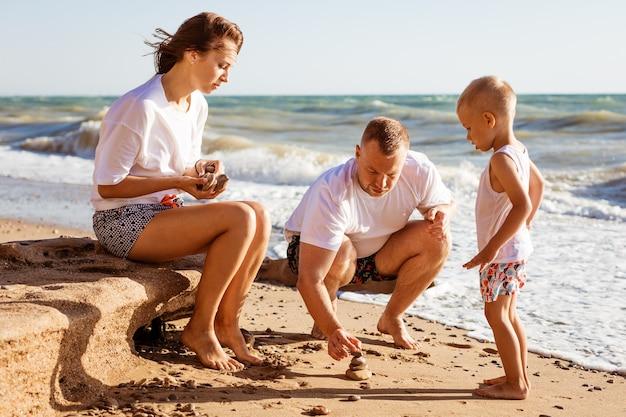 若い家族は、日当たりの良い夏に海のそばで幼い息子と一緒に砂の上で幸せな両親を描いています...