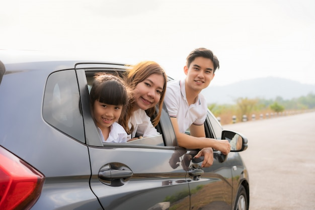 Young family looking over the window in a parked car on a road