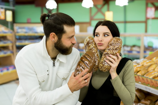 A young family, a man and a woman choose bread in a large supermarket.