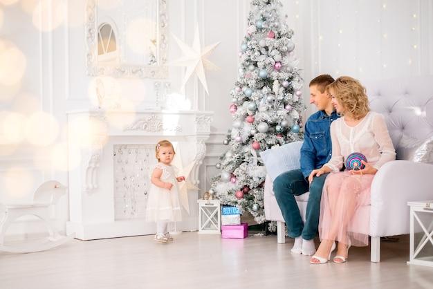 若い家族。ママ、パパ、そして小さな娘がクリスマスツリーを飾ります。クリスマスの準備。