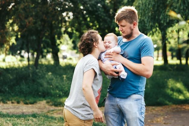 若い家族、母親の父、赤ちゃんの息子、公園で幸せなポーズ
