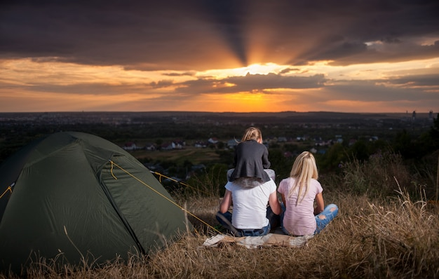 Young family near the tent enjoying a beautiful sunset