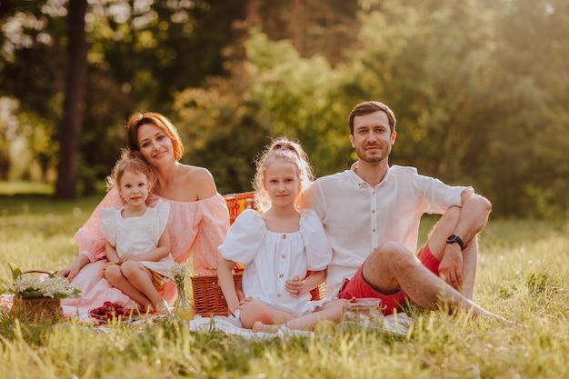 公園でピクニックをしている4人の若い家族。夏時間。コピースペース。