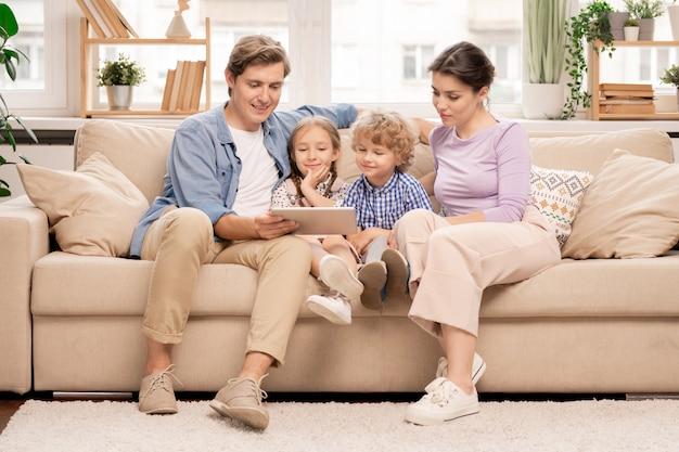 Молодая семья из четырех человек отдыхает на диване в гостиной и смотрит фильм или мультфильмы