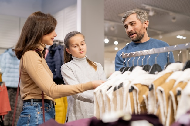 Молодая семья из трех человек выбирает новый теплый меховой жилет, стоя у стойки в отделе повседневной одежды в торговом центре