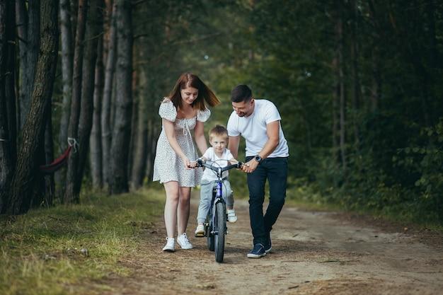 森の中でピクニックをしている若い家族、夫、妻、幼い息子、息子に自転車に乗ることを教える