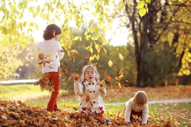 晴れた日に秋の公園を散歩している若い家族。一緒にいる幸せ。