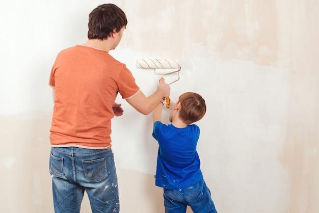 若い家族の絵画の家の壁。父と息子が壁を塗っています。彼らの新しい家を改装する幸せな家族。父は息子にローラーで壁を塗る方法を示しています。