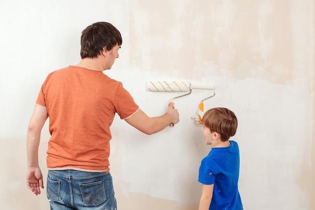 Молодая семья рисует стену дома. отец и сын красят стену.