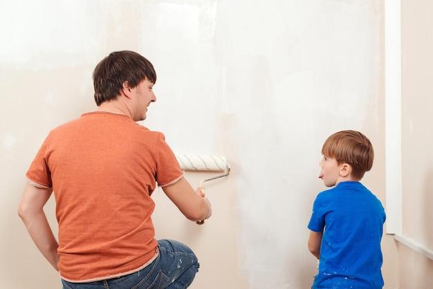 Молодая семья рисует стену дома