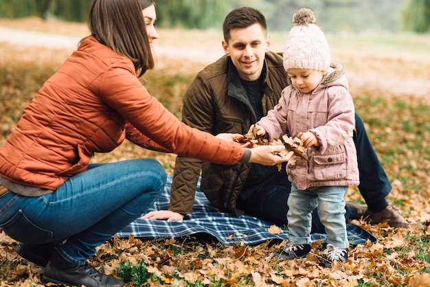 Young family playing with leaves in autumn forest