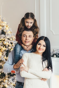 Young family poses before a shiny Christmas tree in a cosy luxury room