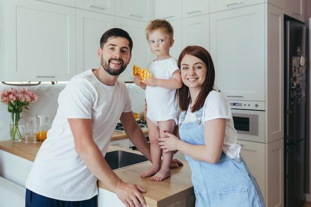Молодая семья готовит завтрак вместе, муж, женщина и дети