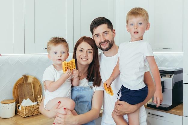 Молодая семья готовит завтрак вместе, муж, женщина и двое детей