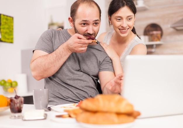 아침 식사를 하는 아침에 이메일로 좋은 소식을 받는 젊은 가족. 아침에 집에서 성공적인 기업가, 승자와 사업 승리