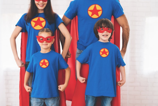 Young family in red and blue suits of superheroes.