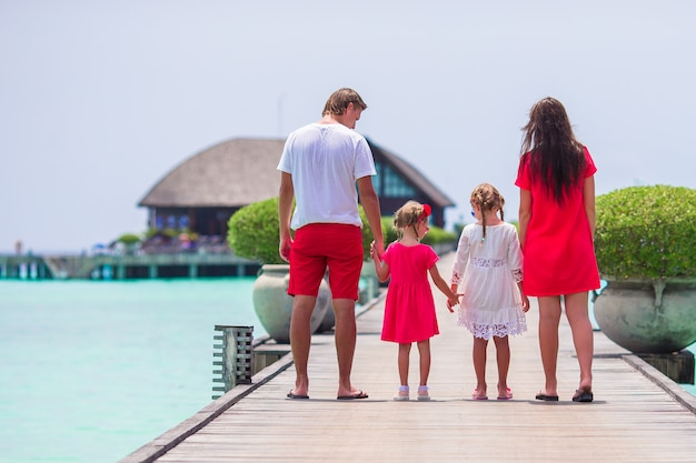 Young family in red on wooden jetty in maldives