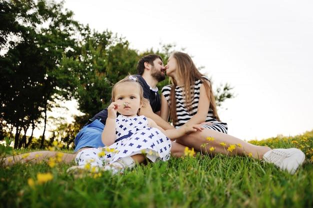 잔디에 공원에서 편안한 젊은 가족. 어린 소녀는 잔디에서 재생