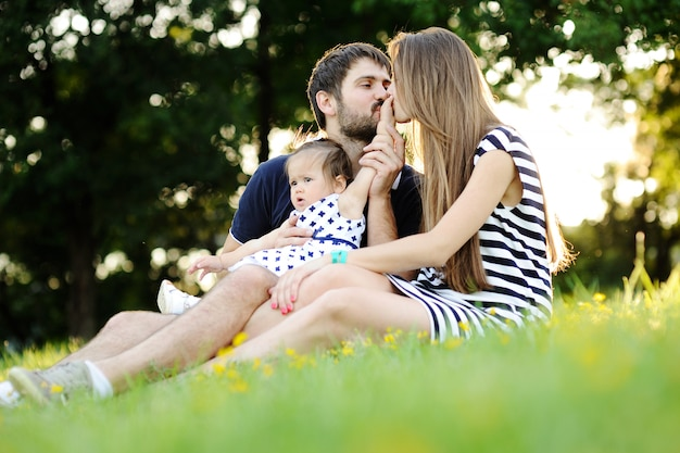 Young family relaxing in the park on the grass. mom and dad kiss his hand a small daughter