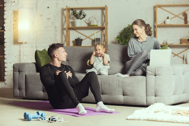 Молодая семья отдыхает после тренировки дома