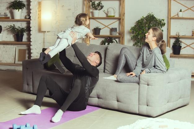 自宅でフィットネス有酸素ヨガをした後の若い家族の休息スポーティなライフスタイルがアクティブになります...