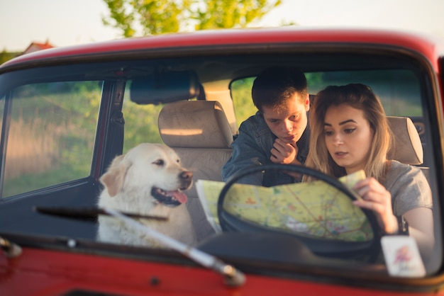 Young family on a road trip with their dog