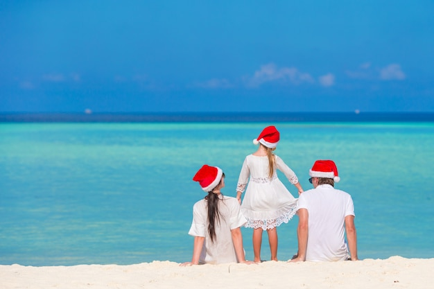 Young family in santa hats during christmas vacation