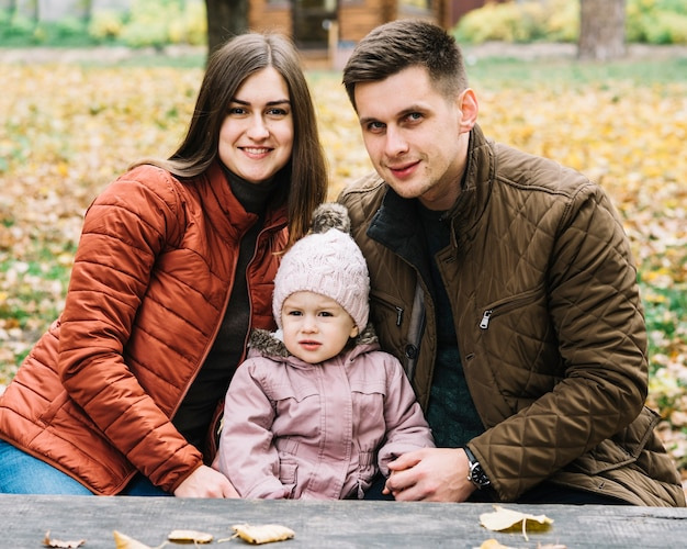 Young family sitting on bench in autumn park